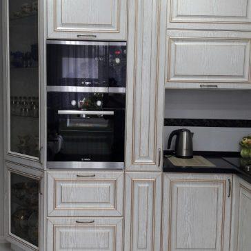 Классическая кухня с витриной для посуды, высоким карго и современной техникой - образец сочетания классического стиля и современных направлений