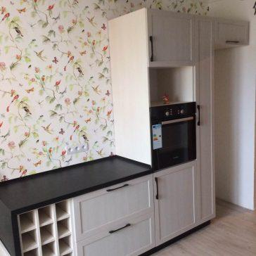 Элемент кухни из рамочного МДФ в сочетании с бутылочницей создаёт эффект деревенского стиля в интерьере кухни с деревянными балками и яркими стенами