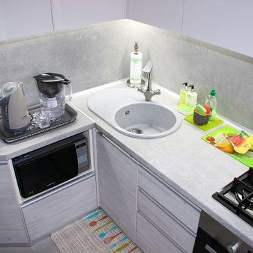 Кухня в серых тонах служит хорошим фоном для ярких аксессуаров. Скиналь из МДФ в цвет столешницы гармонично сочетается с фасадами из итальянского ДСП Cleaf древесной структуры