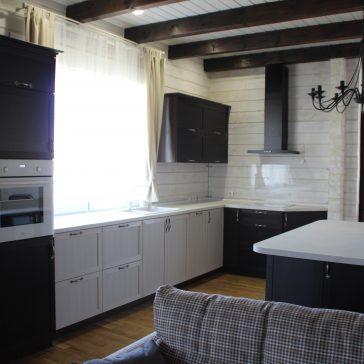 Кухня с комбинированными фасадами из рамочного МДФ и столешницей из искусственного камня в частном доме. Широкий остров служит отличным дополнением к интерьеру в современном классическом стиле