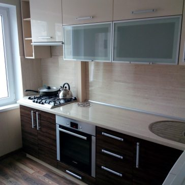"""Пример кухни для планировки """"чешки"""". Срезанный угол столешницы помогает обойти низко расположенное окно, а глянцевые фасады с элементами стекла зрительно увеличивают пространство"""