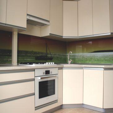 Фасады из глянцевого акрила в сочетании с врезной ручкой - классический пример современной кухни. Акцент создает фотопечать на закаленном стекле с изображением морского пейзажа