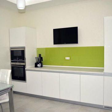 Ультрасовременная кухня в минималистичном стиле с фасадами из крашеного МДФ. Монохромные цвета разбавлены скиналью из закаленного секла ярко-салатового цвета
