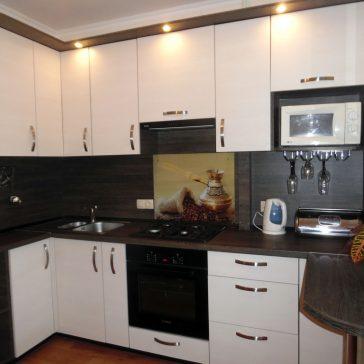 Замечательный контраст, созданный белыми фасадами из ЛДСП и темной структурой дерева столешницы и скинали. Кухня продолжается столешницей, совмещенной с подоконником, а акцентом служит элемент фотопечати на закаленной стекле.