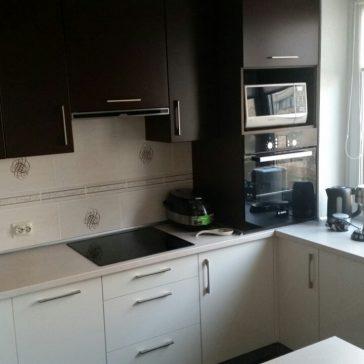 Контрастная кухня тёплых тонов с совмещенным подоконником из цельной столешницы. Фасады - крашеный МДФ и глянцевые панели
