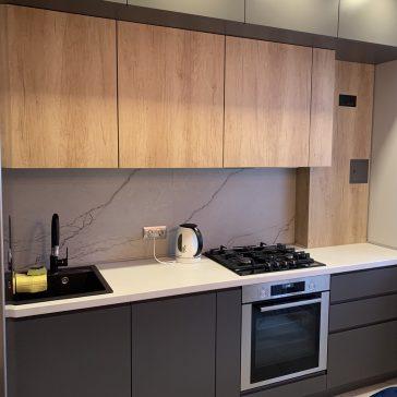 Небольшая кухня из крашенного МДФ в сочетании с древесной структурой ЛДСП