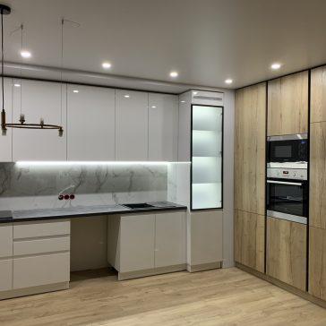 Г-образная кухня с крашенными фасадами из МДФ и пеналами из ЛДСП.
